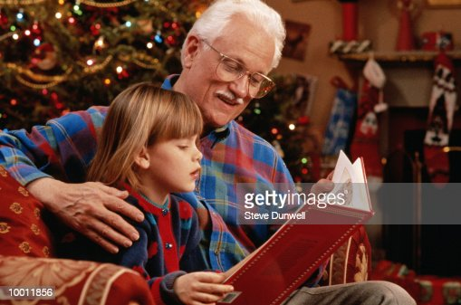 GRANDFATHER READING TO GIRL BY CHRISTMAS TREE : Stock Photo