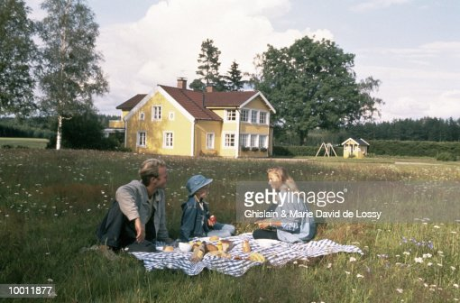 FAMILY PICNICKING IN FRONT OF HOUSE : Stock Photo