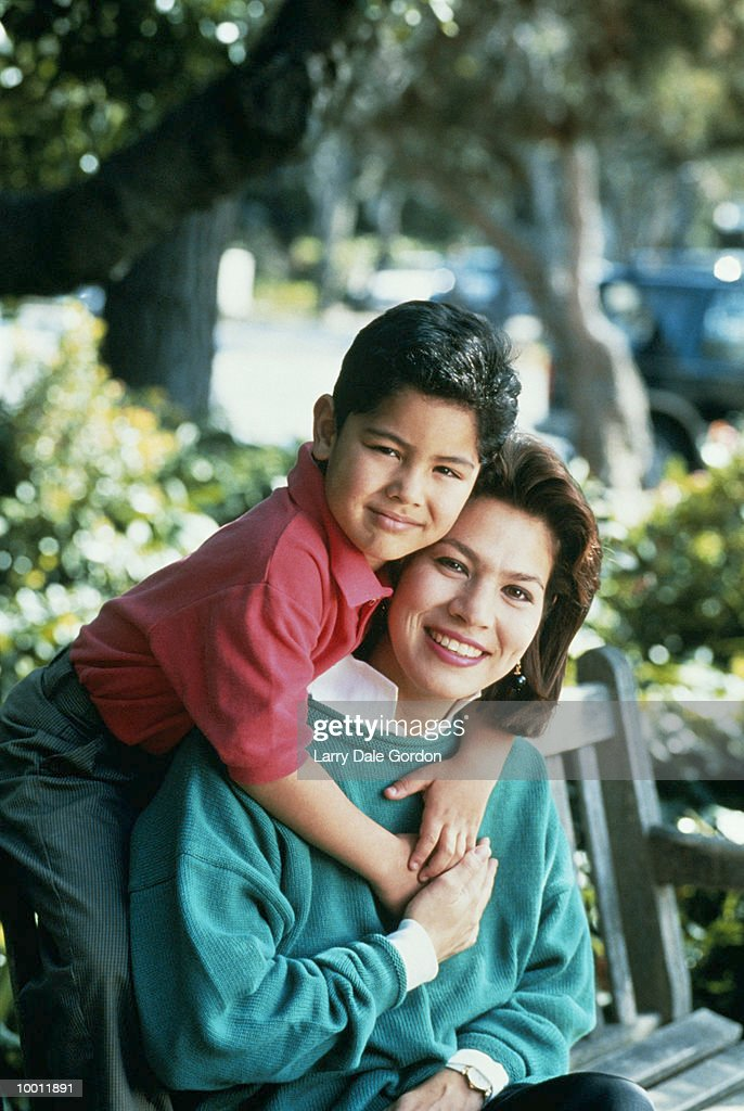 YOUNG HISPANIC BOY WITH ARMS AROUND MOTHER : Stock Photo