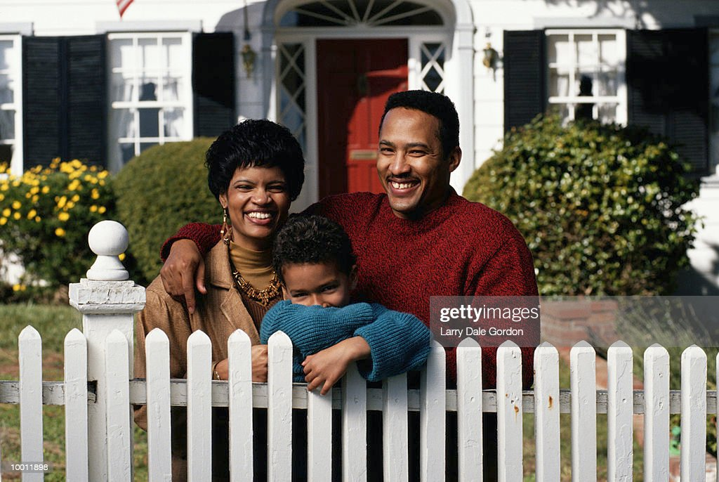 BLACK FAMILY IN FRONT OF HOUSE AT FENCE : Stock Photo