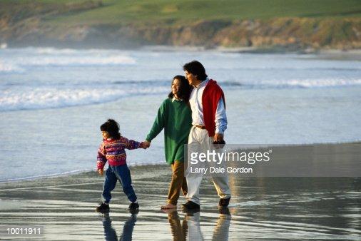 HISPANIC FAMILY WALKING ON BEACH : Stock Photo