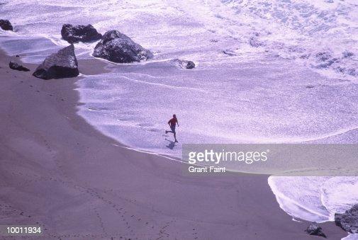 MAN RUNNING IN SURF IN CALIFORNIA : Stock Photo