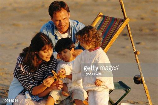 FAMILY AT BEACH INSPECTING STARFISH : Stock Photo