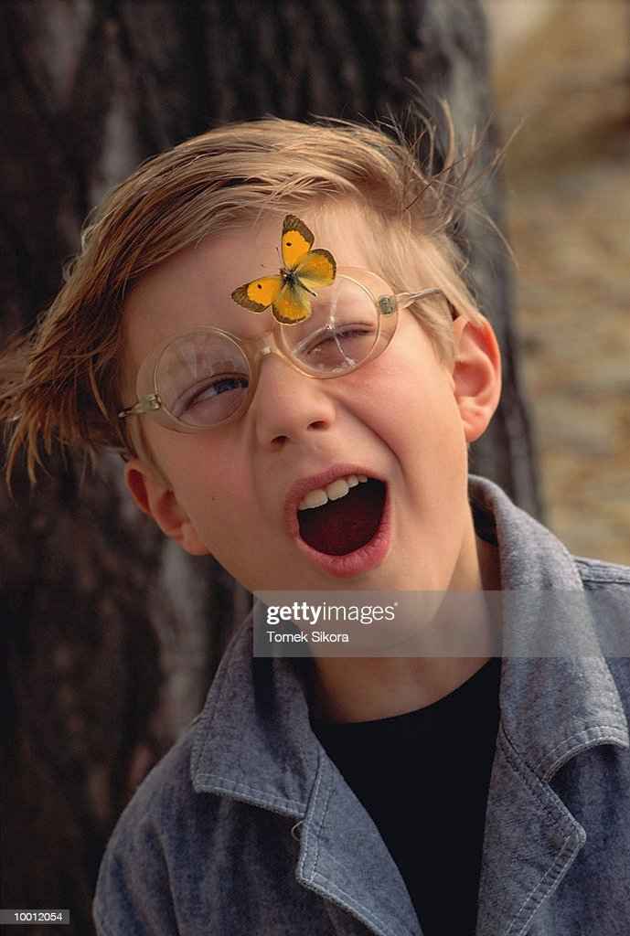 BOY WITH MOUTH AGAPE & BUTTERFLY ON GLASSES : Stock Photo