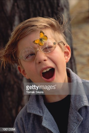BOY WITH MOUTH AGAPE & BUTTERFLY ON GLASSES : Foto de stock