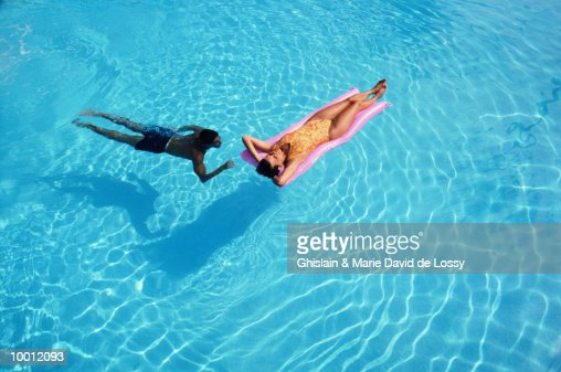 MAN SWIMMING TO WOMAN ON RAFT : Stock Photo