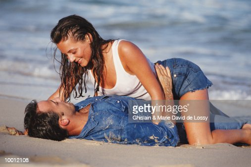 INTIMATE COUPLE LYING IN SURF ON BEACH : Foto de stock