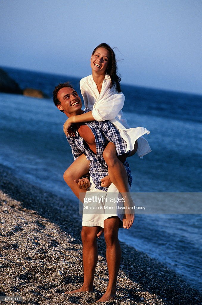 MAN GIVING WOMAN PIGGYBACK RIDE : Stock Photo