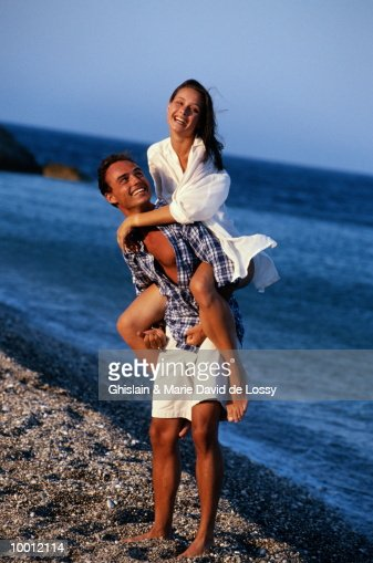 MAN GIVING WOMAN PIGGYBACK RIDE : Foto de stock