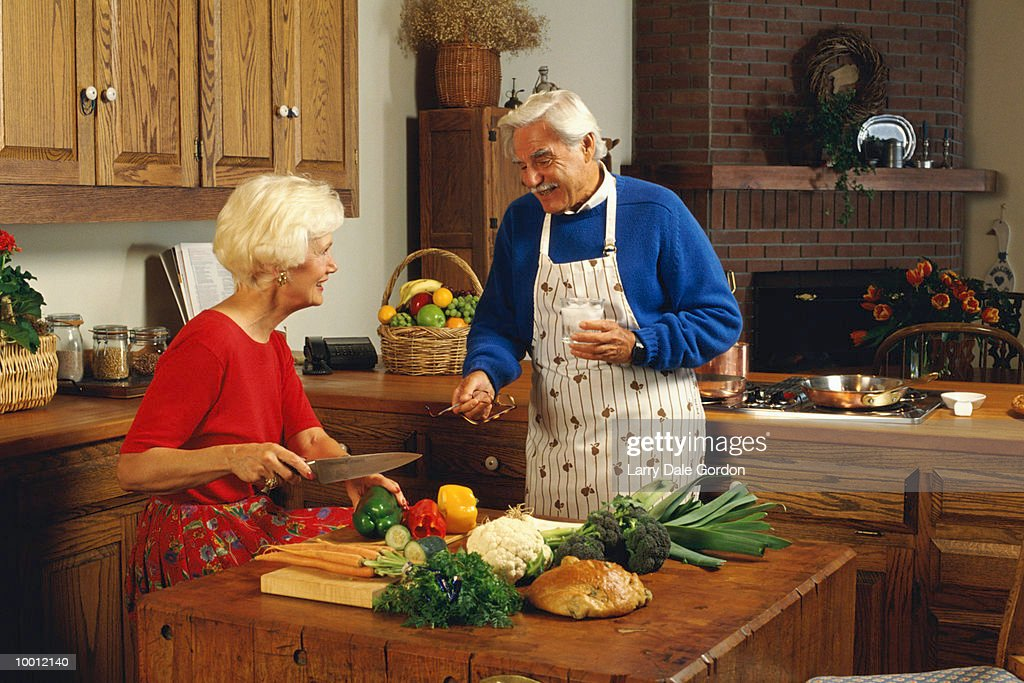 MATURE COUPLE PREPARING DINNER : Stock Photo