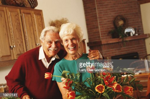 PORTRAIT OF A MATURE COUPLE IN HOME WITH FLOWERS : Stock-Foto