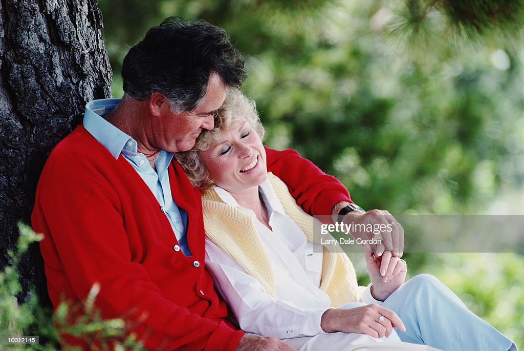 MIDDLE-AGED COUPLE RELAXING AGAINST TREE : Stock Photo