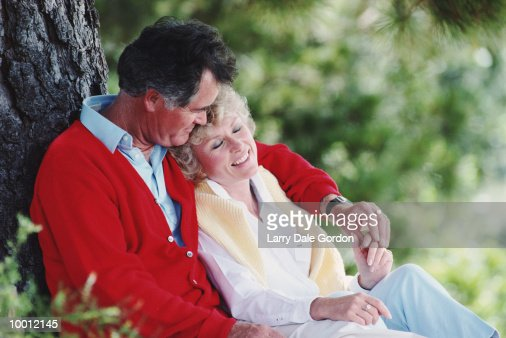 MIDDLE-AGED COUPLE RELAXING AGAINST TREE : Stock-Foto