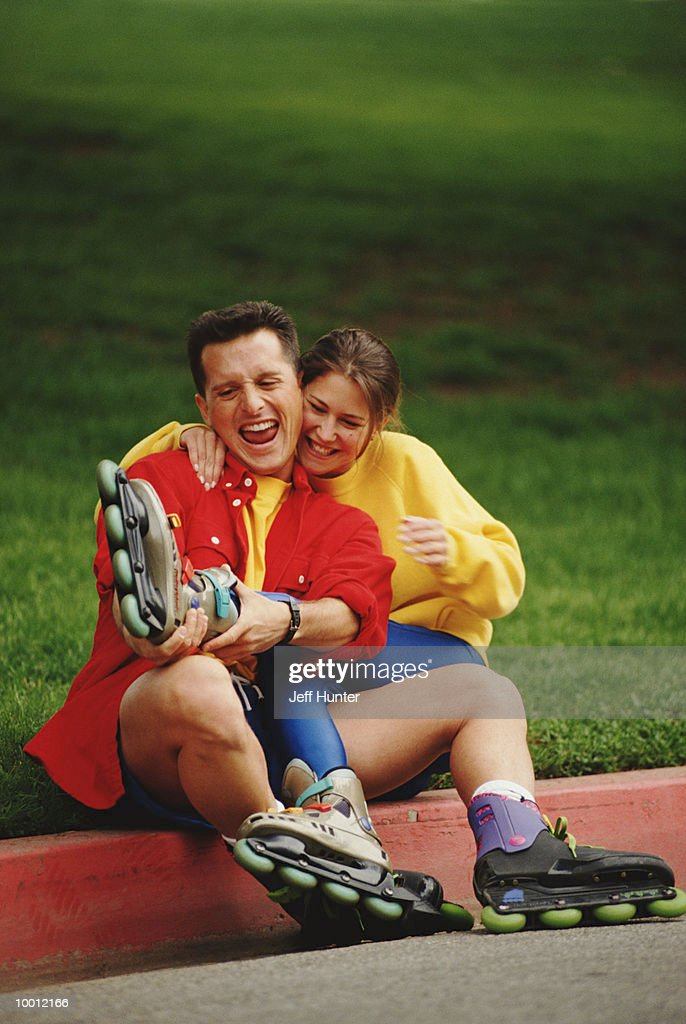 PLAYFUL COUPLE WITH ROLLERBLADES ON CURB : Stock-Foto