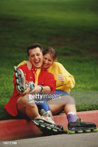 PLAYFUL COUPLE WITH ROLLERBLADES ON CURB : Stock Photo