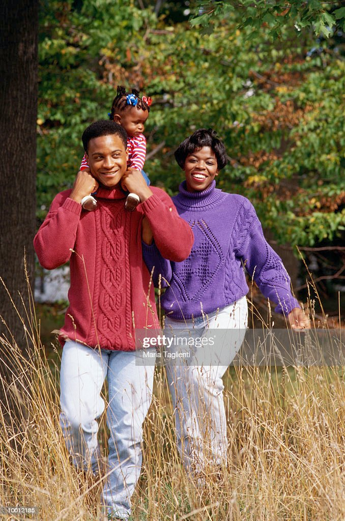 BLACK FAMILY ON WALK IN FIELD : Stock Photo