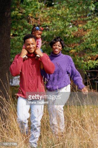 BLACK FAMILY ON WALK IN FIELD : Stock Photo