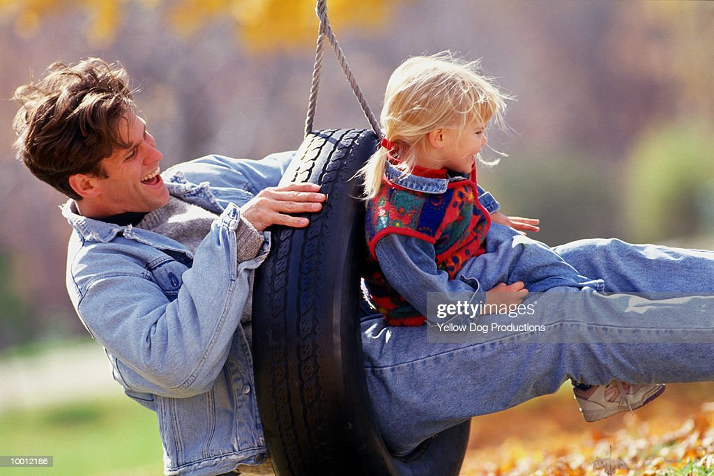 FATHER & DAUGHTER ON TIRE SWING IN FALL : Stock Photo