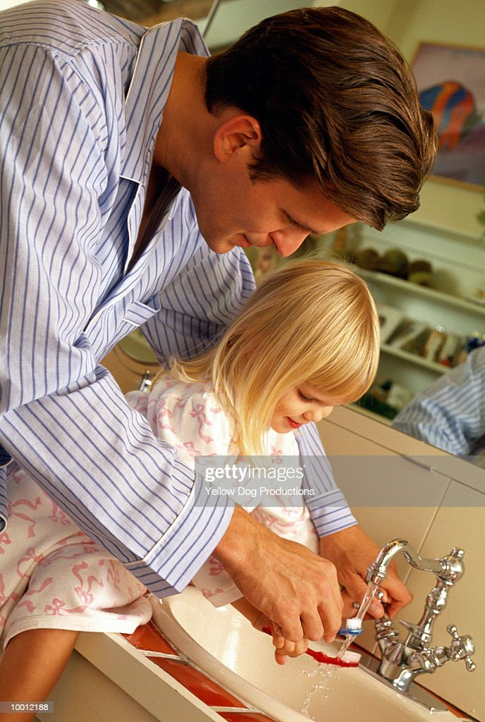FATHER & DAUGHTER RINSING TOOTHBRUSHES : Stock Photo