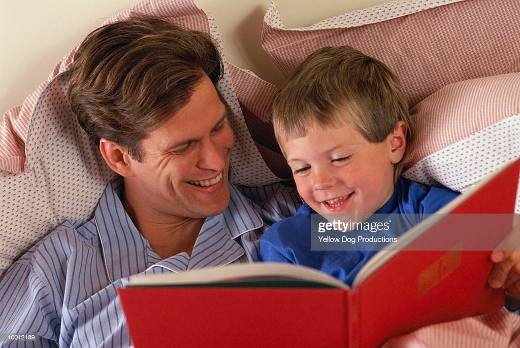 FATHER & SON IN BED READING BOOK : Foto de stock