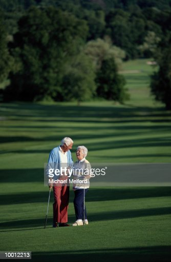MATURE COUPLE ON GOLF COURSE : Stock Photo