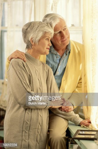 MATURE COUPLE LOOKING OUT WINDOW IN HOME : Stock Photo