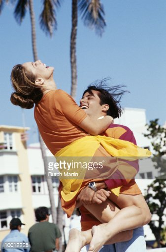 PLAYFUL YOUNG COUPLE ON BEACH : Stock-Foto
