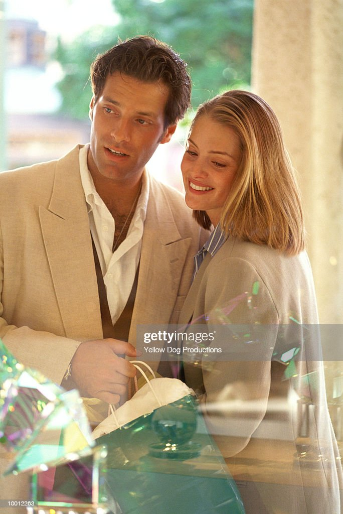 COUPLE WITH SHOPPING BAG & WINDOW REFLECTIONS : Stock-Foto