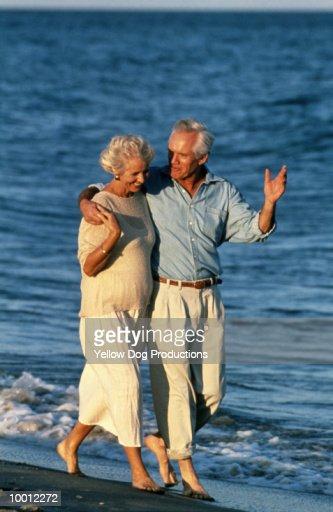 MATURE COUPLE WALKING ON BEACH AT SUNSET : Stock Photo