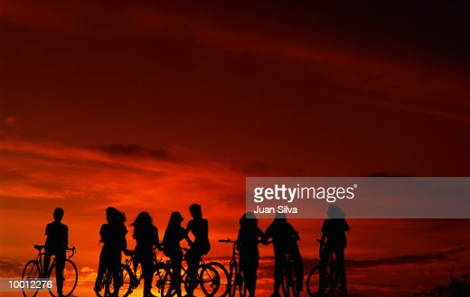 SILHOUETTE OF TEENAGERS ON BICYCLES AT SUNSET : Stock-Foto