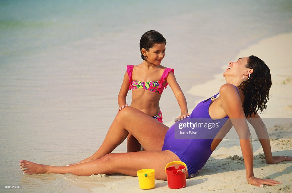 PREGNANT MOTHER WITH DAUGHTER ON BEACH : Stock Photo