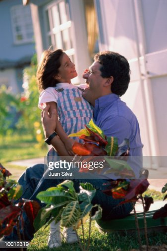 FATHER PLAYING WITH DAUGHTER IN GARDEN : Stock Photo