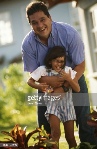FATHER PLAYING WITH DAUGHTER OUTDOORS : Foto de stock