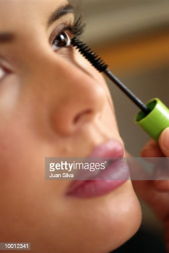CLOSE-UP OF A WOMAN APPLYING MASCARA : Stock Photo