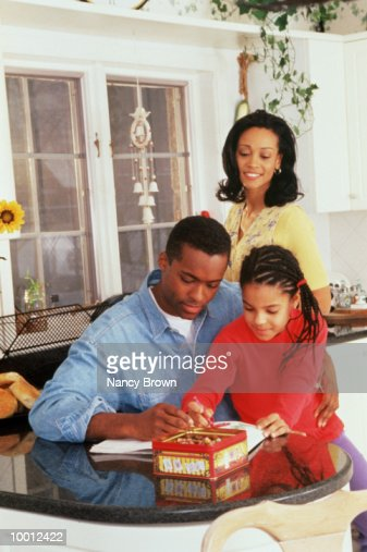 BLACK PARENTS WITH DAUGHTER IN KITCHEN : Stock Photo