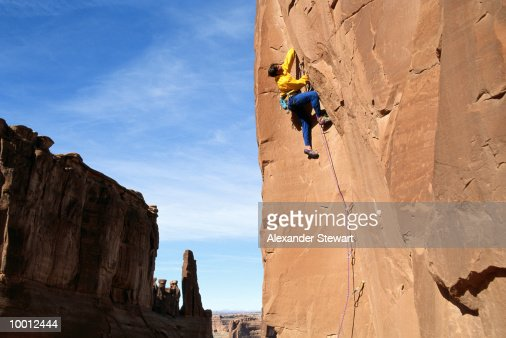 MALE ROCK CLIMBER AT ARCHES NATIONAL PARK IN UTAH : Stock-Foto