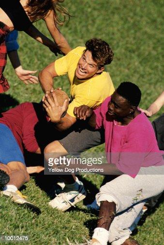 MULTI-ETHNIC YOUNG MEN PLAYING FOOTBALL : Foto de stock