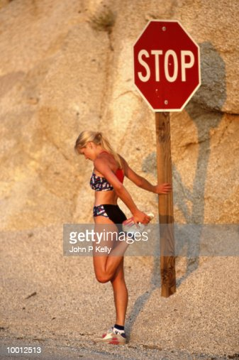 WOMAN STRETCHING BY STOP SIGN IN MOUNTAINS : Stock-Foto