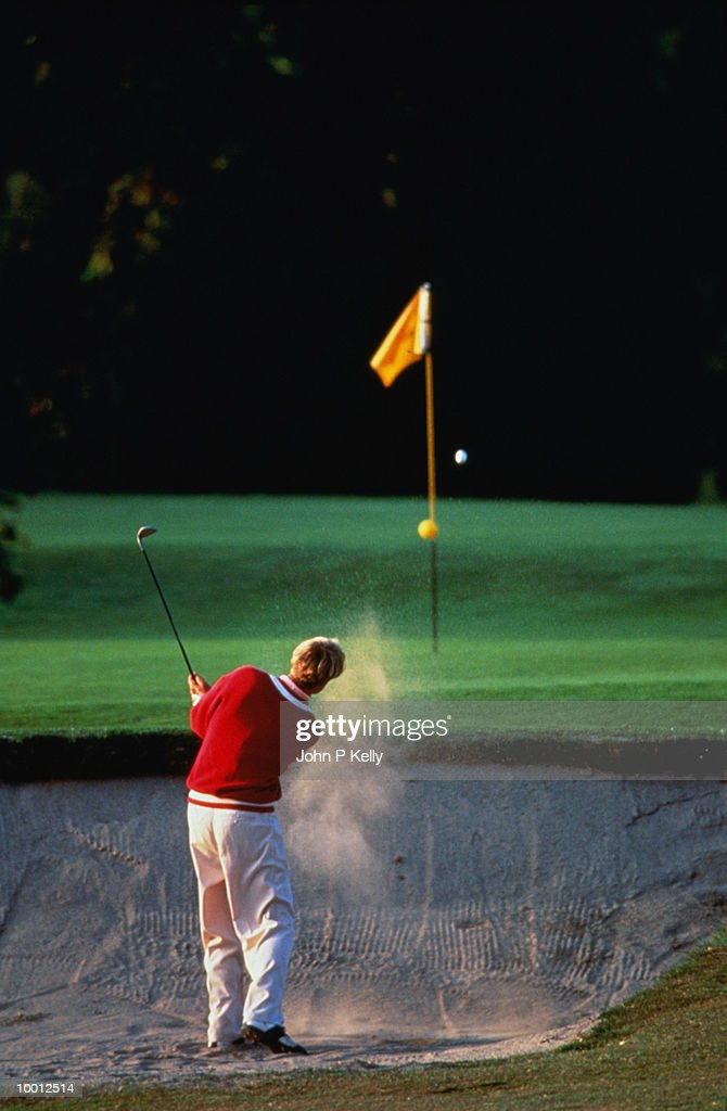 BACKVIEW OF A GOLFER IN SAND TRAP : Stock Photo