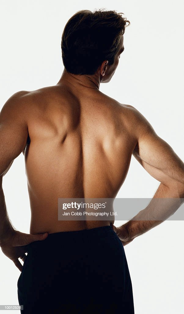 BACKVIEW OF A SHIRTLESS MAN WITH ARMS AKIMBO : Stock-Foto