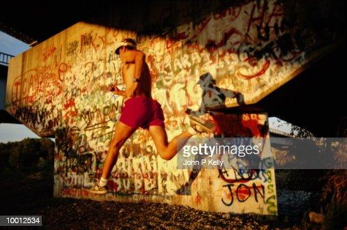 MAN RUNNING BY GRAFFITI BRIDGE WALL : Stock Photo