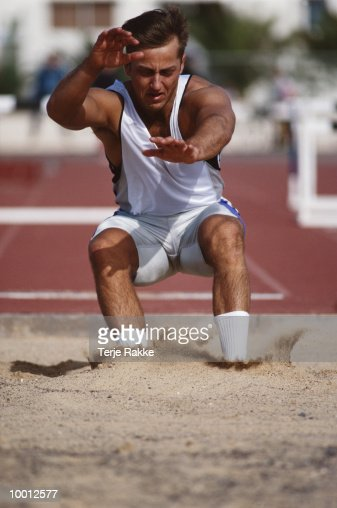 MALE ATHLETE IN LONG JUMP COMPETITION : Stock Photo