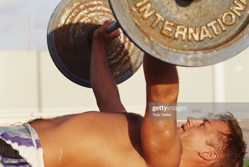 MAN ON BACK LIFTING BARBELL : Stock Photo