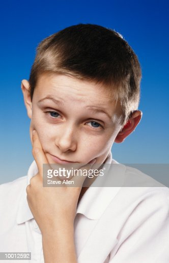BOY PONDERING THOUGHT WITH CHIN IN HAND : Stock-Foto