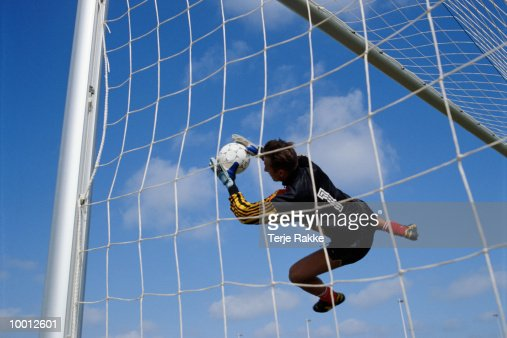 GOALIE IN MIDAIR CATCHING SOCCER BALL : Stock-Foto