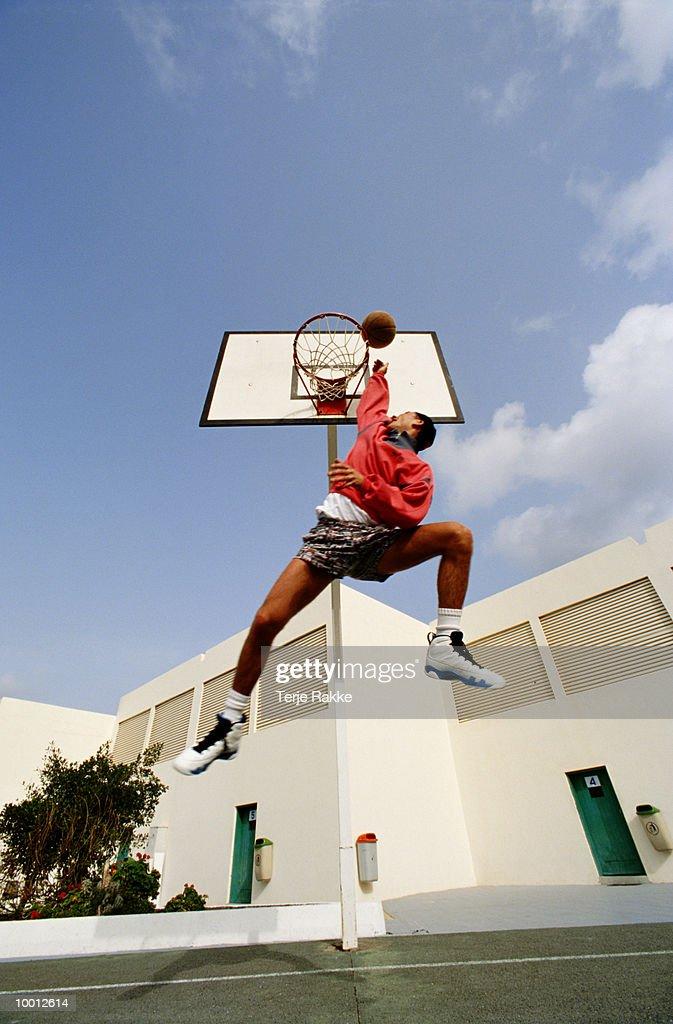 MAN IN MIDAIR PLAYING BASKETBALL : Stock-Foto