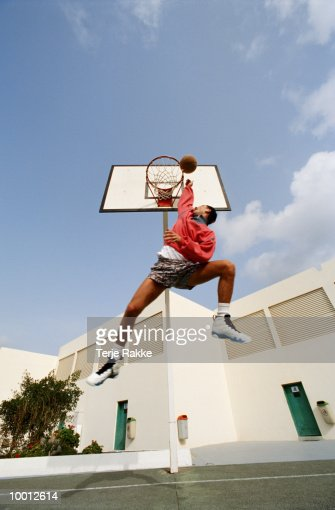 MAN IN MIDAIR PLAYING BASKETBALL : Stock Photo