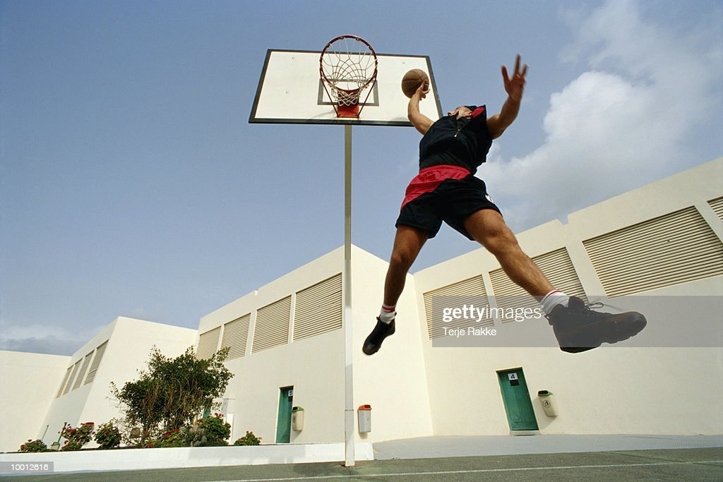 MAN WITH BASKETBALL IN MIDAIR BY OUTDOOR NET : Stock Photo