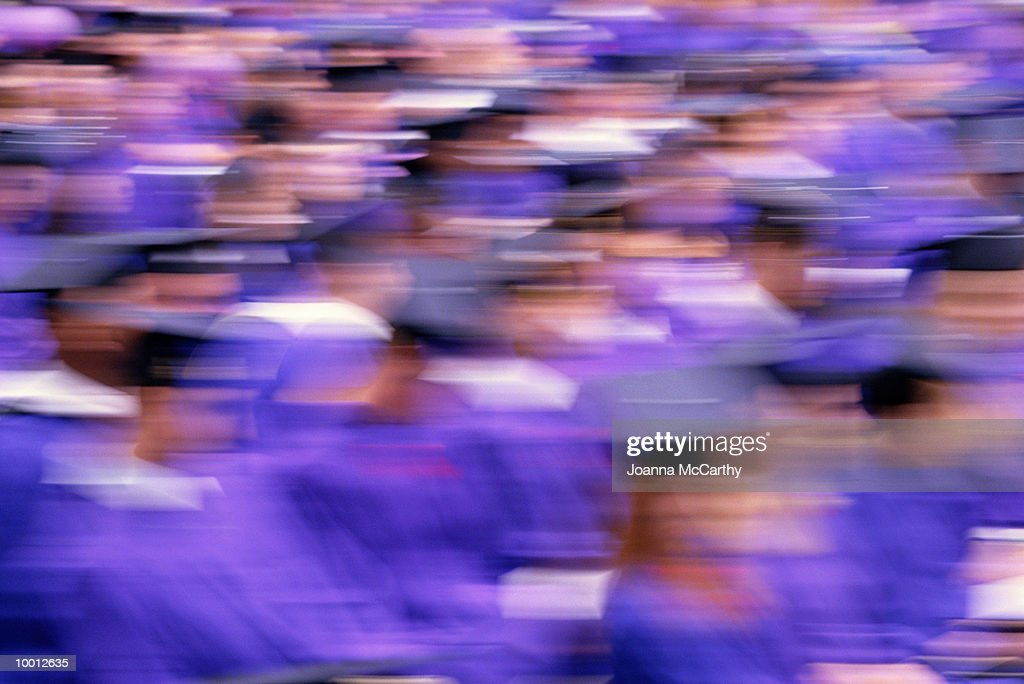 SEATED GRADUATES IN CAPS & GOWNS IN BLUR : Stock Photo