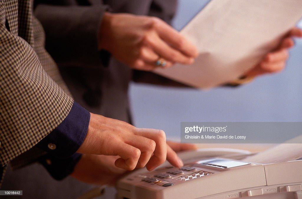 SENDING INFORMATION ON FAX MACHINE : Stock Photo